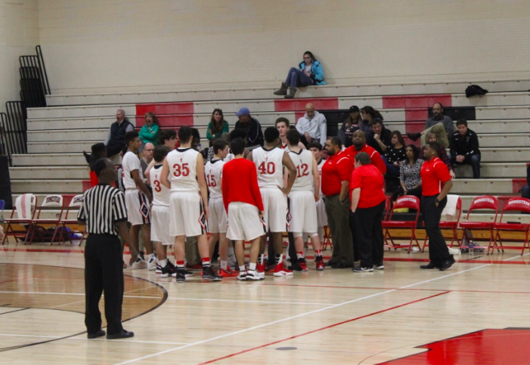 The boys varsity basketball team huddles during home game against Wisconsin  Lutheran. - Basketball Team Huddle PNG