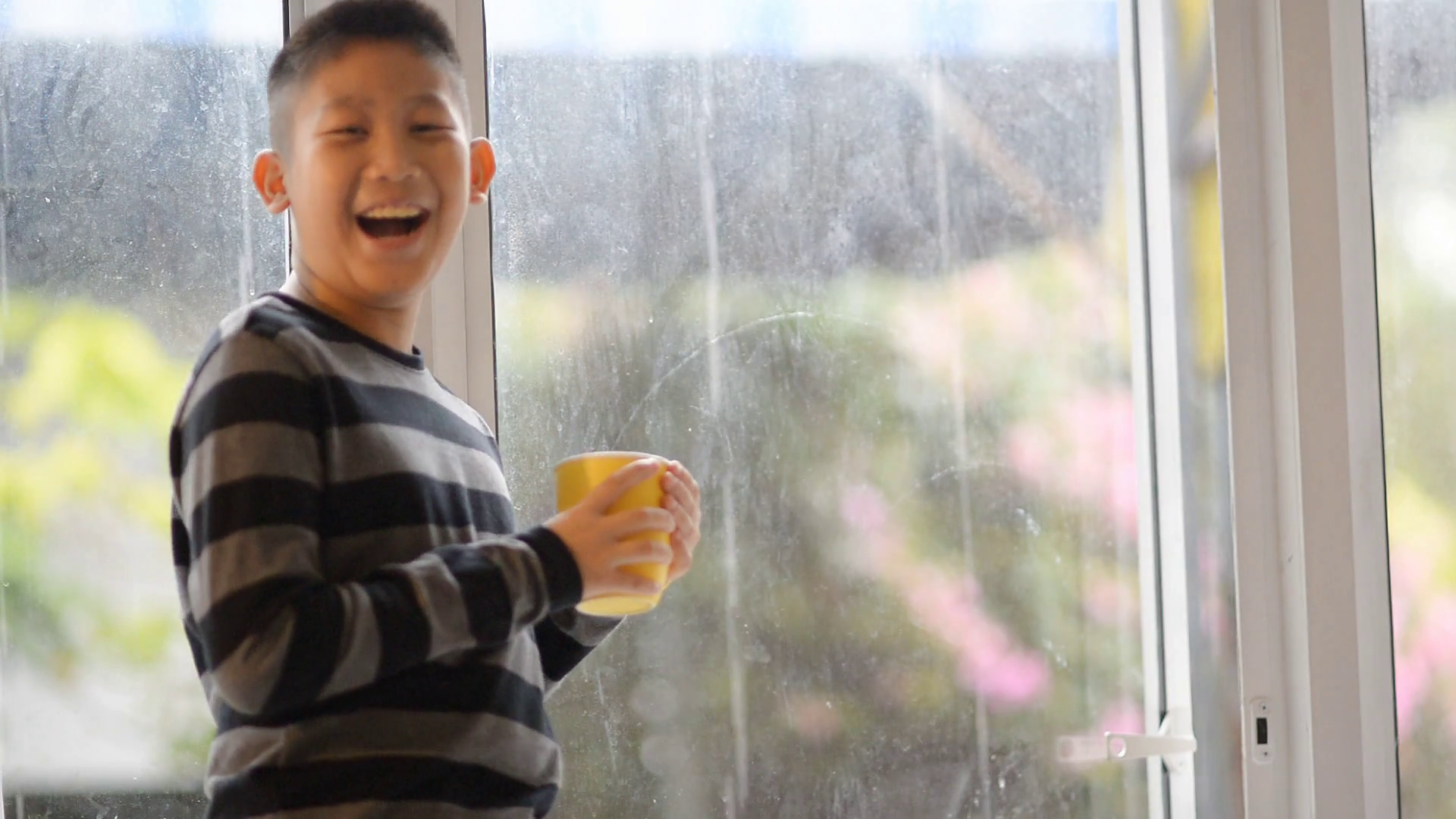 Asian boy drinks tea, juice or hot chocolate standing at the windowsill and looking  out window in rainy day Stock Video Footage - VideoBlocks