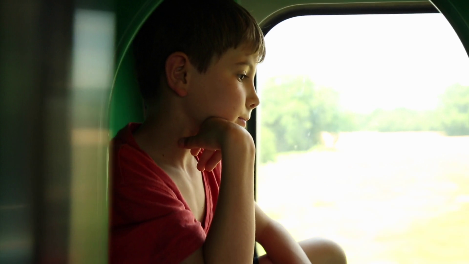 Contemplative child daydreaming while looking out train window. Kid looking  out train window thinking with a thoughtful look on face.