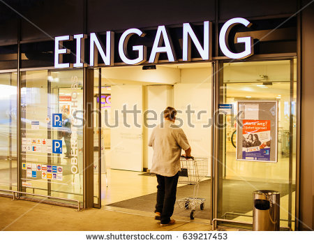 KEHL, GERMANY MAR 30, 2017: Man with shopping cart above Eingang signage  translated - Edeka Vector PNG