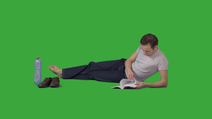 Attractive barefooted man is lying on side and reading book. Footage with  alpha channel. - Feet PNG HD