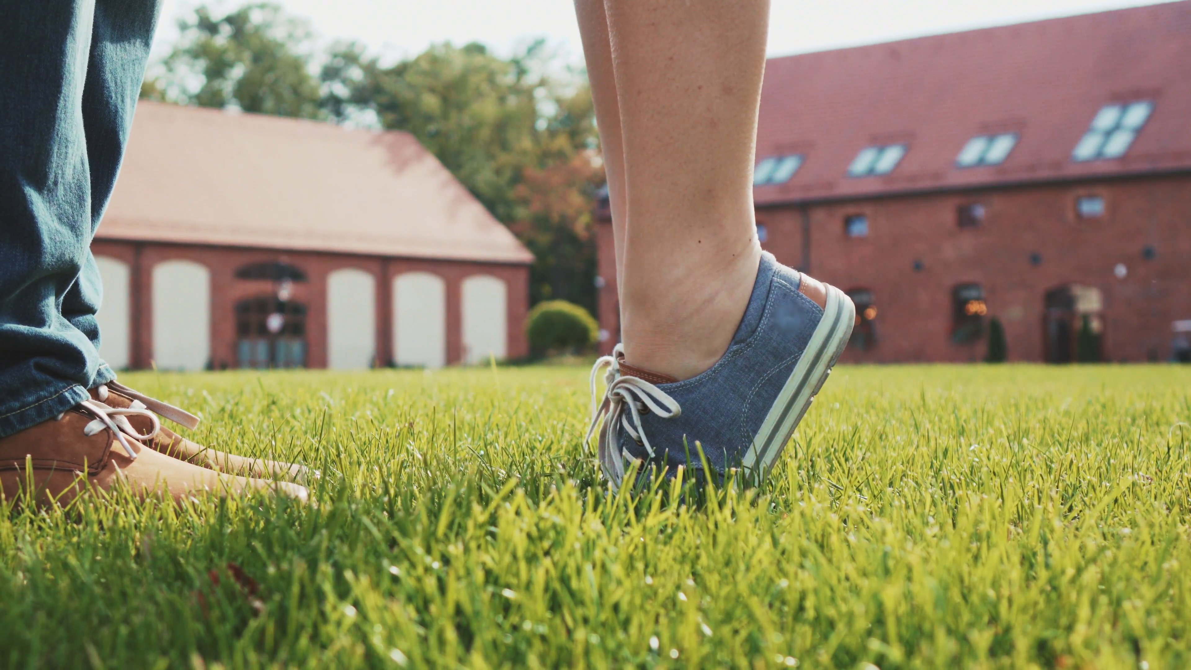 Close up of feet and legs as woman is tip toeing for a kiss. Romantic  Couple kissing on a green grass lawn outdoors. 4K Ultra HD. - Feet PNG HD