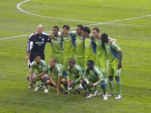 Eleven soccer players wearing green jerseys and green shorts posing in two  rows on a grass. Starting players before a 2009 Sounders FC match - Seattle Sounders Fc PNG