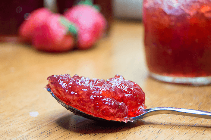 Once the jelly has reached the desired temperature, transfer the jelly to  sanitized jelly jars, leaving about 1/4 inch of space at the top. - Strawberry Jam PNG
