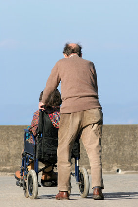 Rear view oif an elderly man pushing an elderly female in a wheelchair on a  pavement with a blue sky to the rear. - Wheelchair Elderly PNG